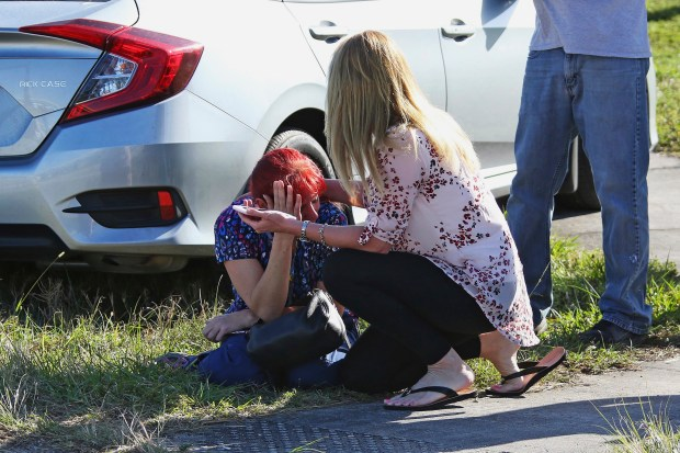 A woman consoles another as parents wait for news regarding a shooting at Marjory Stoneman Douglas High School in Parkland, Fla., on Wednesday. At least 17 people were killed in the shooting.