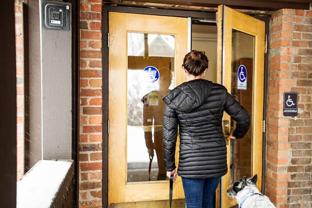 Gabriella Rand, who works for the Community Development Department at Aspen City Hall enters through the back door of the building on Thursday.