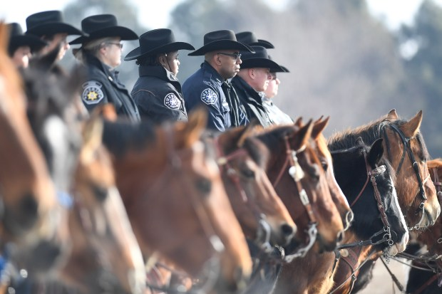 Mounted law enforcement officials watch the ...