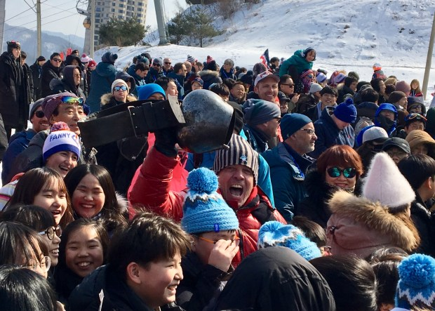 Marcelo Ferreira clangs a huge cowbell amidst a horde of chanting kids to celebrate the run of his son, Alex Ferreira, who won silver in the PyeongChang halfpipe on Thursday. Photo by Jason Blevins / The Denver Post