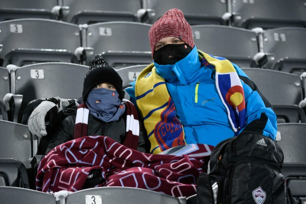 Soccer fans try to stay warm ...