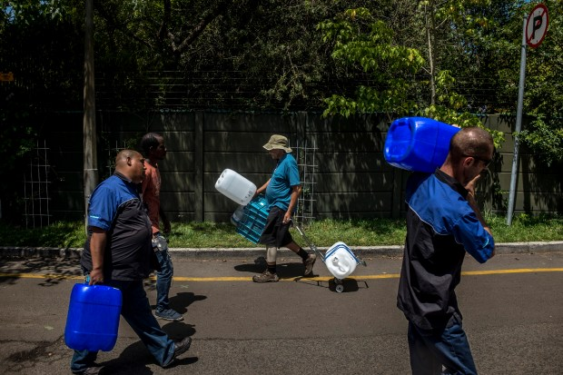 People refill water bottles on Feb. 14, 2018, at the Newlands Spring tap, one of the fresh mountain springs in Cape Town, South Africa. Within the next few months, the city's taps could run dry.