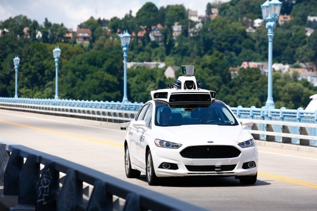 Uber employees test a self-driving Ford Fusion hybrid car in Pittsburgh on Aug. 18, 2016.