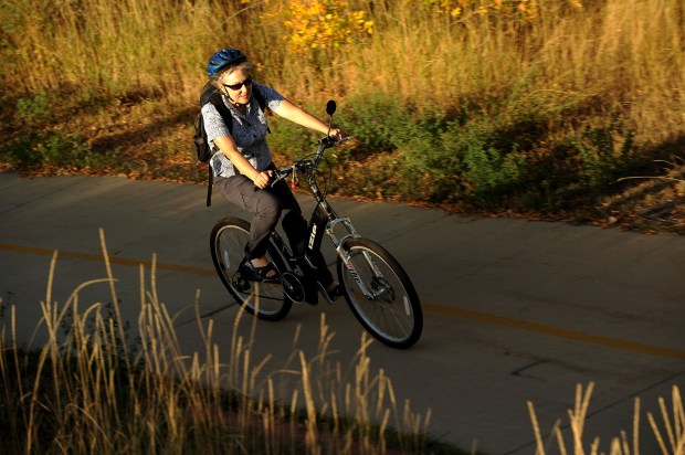 A woman rides an e-bike on a paved trail near Boulder.