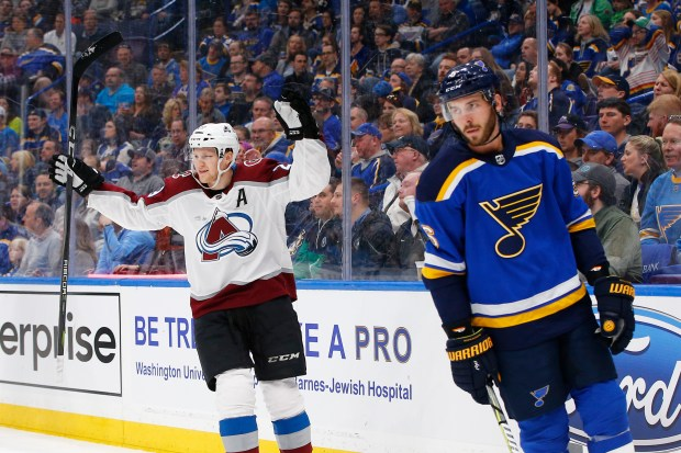 Colorado Avalanche's Nathan MacKinnon, left, reacts ...