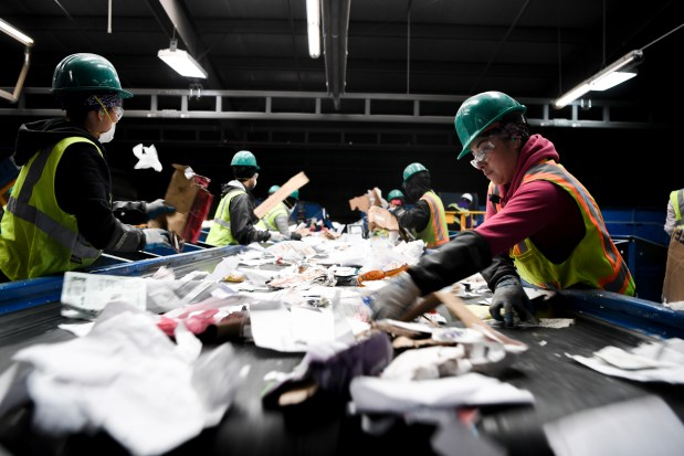 Workers separate paper and other contaminants ...