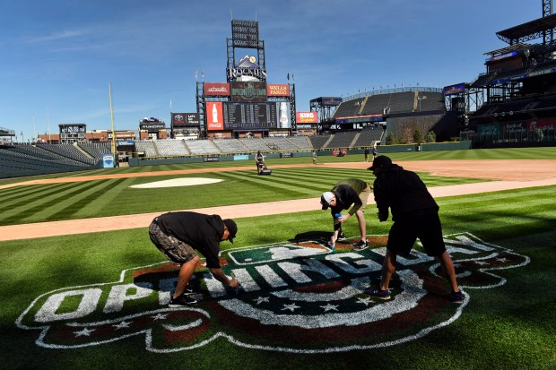 Members of the Colorado Rockies' grounds crew prepare Coors Field for opening day of baseball season on April 6, 2017.