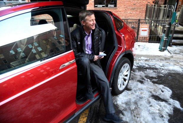 Colorado Gov. John Hickenlooper sits in a Tesla Model X electric car before a press conference on Jan. 24. The legislature is considering a bill that would end tax credits on the purchase of electric vehicles.