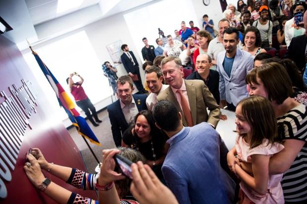 AURORA, CO - MAY 30: Gov. John Hickenlooper (D) takes a picture with other lawmakers and other attendants after signing a bill on May 30, 2018 at Community College of Aurora in Aurora, Co. The bill aims to give instate tuition to immigrants who worked with the US military before moving to the United State and other refugees. (Photo by Shaban Athuman/The Denver Post)