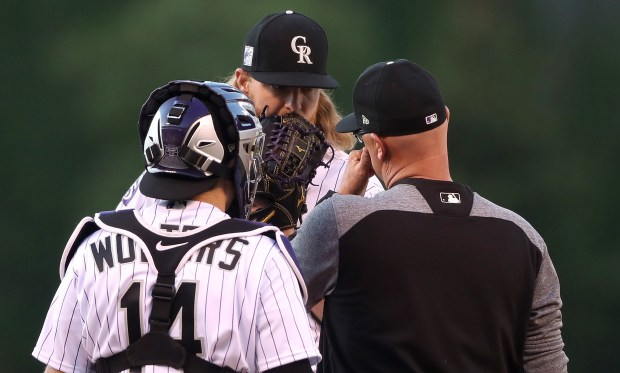 Starting pitcher Jon Gray #55 of the Colorado Rockies confers with catcher Tony Wolters #14 and pitching coach Steve Foster in the first inning against the Los Angeles Angels of Anaheim at Coors Field on May 8, 2018 in Denver, Colorado.
