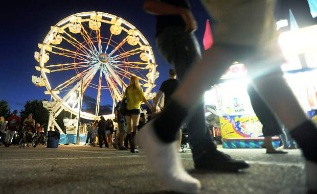 In this 2015 Tribune file photo, carnival-goers walk by the ferris wheel outside the Stampede Arena in Greeley. The Greeley Stampede has recently come under fire for flouting liquor laws, and faces a more formal event review process for this year's event.