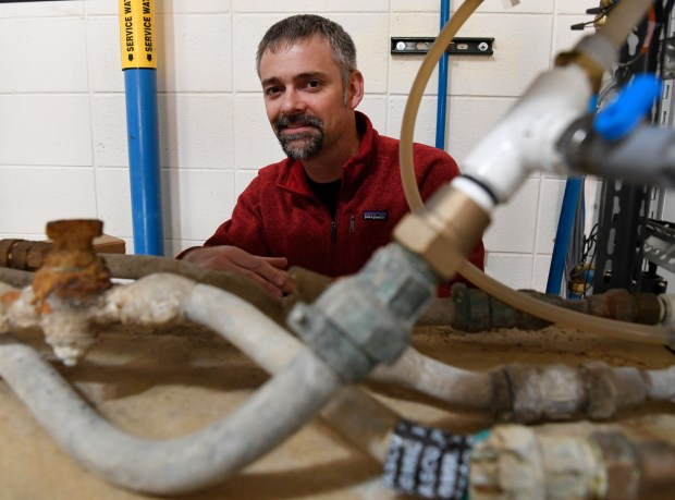 Denver Water engineer Ryan Walsh, project manager for the lead project corrosion control study stands behind shelves of harvested lead water service lines taken from older homes at the Marston Water Treatment Plant May 3, 2018.