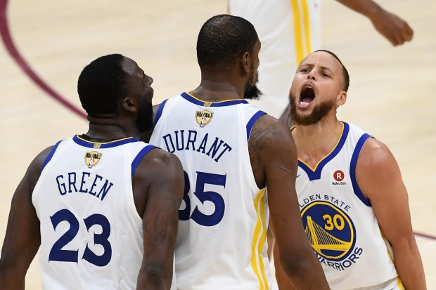 Stephen Curry (30) and Draymond Green (23) of the Golden State Warriors celebrate with Kevin Durant (35) against the Cleveland Cavaliers in the second half during Game Three of the 2018 NBA Finals on June 6, 2018 in Cleveland, Ohio.