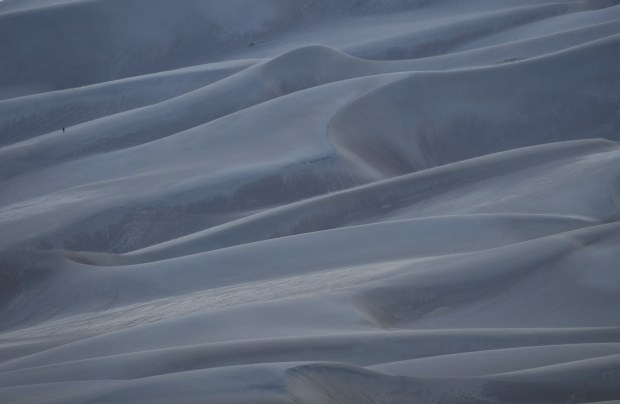A man walks down a dune ...