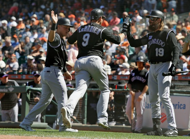 Colorado Rockies' DJ LeMahieu (9) is greeted by teammates Pat Valaika, left, and Charlie Blackmon, right, after hitting a two-run home run off San Francisco Giants relief pitcher Sam Dyson in the ninth inning of a baseball game Thursday, June 28, 2018, in San Francisco. Colorado won the game 9-8.