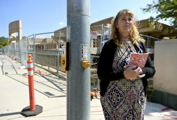 Karen Luebke, an administrative assistant at the Longmont Police Department, waits Wednesday to cross Third Avenue while walking from the Civic Center to the Safety and Justice Center. Jackhammer drilling associated with renovations to the Civic Center is distracting some employees.