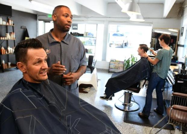 """Ja'mal Gilmore, owner of The Brooklyn Barber Academy, talks to Jay Ferracone during his haircut at the Boulder barber shop on Monday. Gilmore says being a black businessman in Boulder means waking a fine line, being black enough to avoid accusations of whitewashing from black customers, """"but not be too black that white people are afraid of me."""