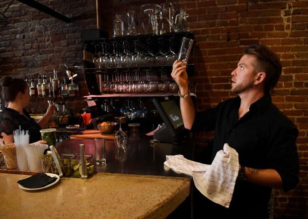 Vesta server Kye Larsen cleans glassware ...