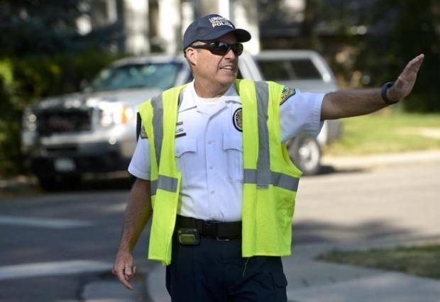 Longmont Police Department Citizen Volunteer Patrol member John Kirkpatrick redirects traffic at the intersection of Longs Peak Avenue and Sunset Street on Wednesday. Traffic was being diverted away from a two-car injury crash at Third Avenue and Sunset Street.