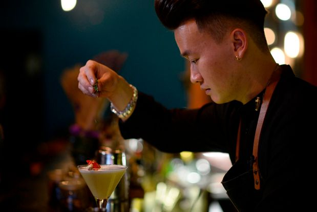 This picture taken on March 21, 2018 shows Ne bartender Nguyen Tuan Anh preparing a pho cocktail in Hanoi.