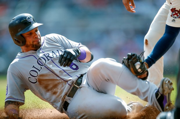 Colorado Rockies Gerardo Parra (8) slides into third where he is tagged out in the ninth inning of a baseball game against the Atlanta Braves, Sunday, Aug. 19, 2018, in Atlanta. The Rockies won the game 4-2.