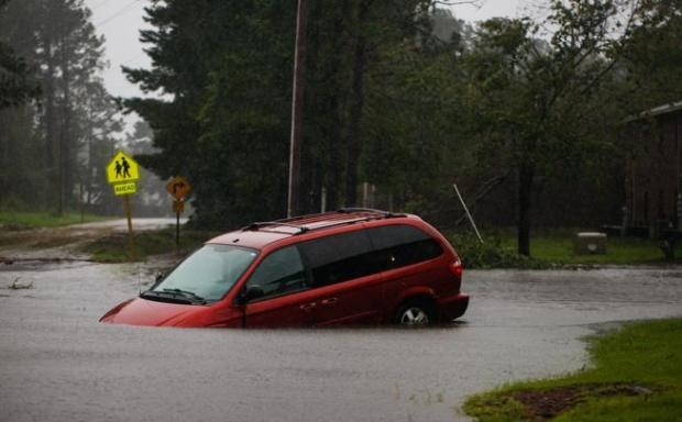 An abandoned minivan sits on a flooded road near New Bern, N.C., on Friday during Hurricane Florence. (Logan Cyrus/ AFP)