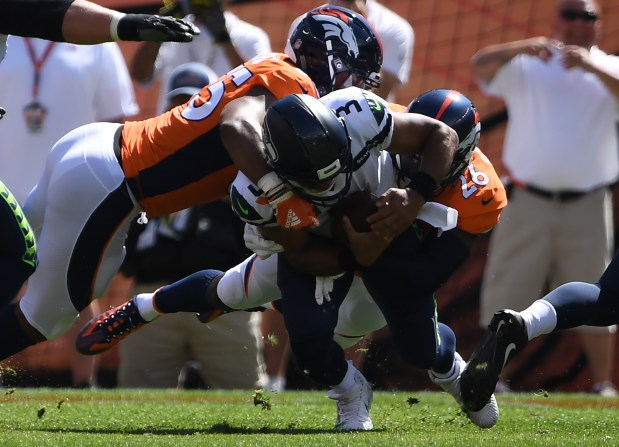 Seattle Seahawks quarterback Russell Wilson (3) is sacked by Denver Broncos defensive back Darian Stewart (26) and Denver Broncos linebacker Bradley Chubb (55) during the first quarter on Sunday, September 9 at Broncos Stadium at Mile High. The Denver Broncos hosted the Seattle Seahawks in the first game of the season.
