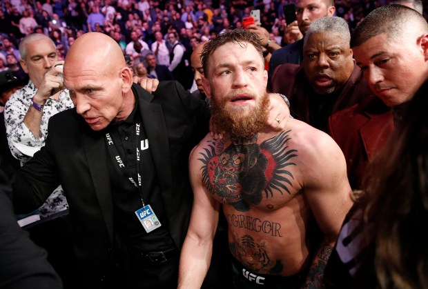 Conor McGregor is escorted from the ...