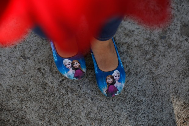 Five-year-old Alexa wears shoes depicting characters ...
