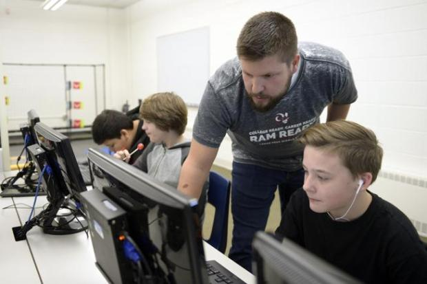 Colin Rickman, Longs Peak Middle School STEM teacher and cybersecurity club co-sponsor, helps seventh-grader Gavin McHenry during a club meeting on Thursday.