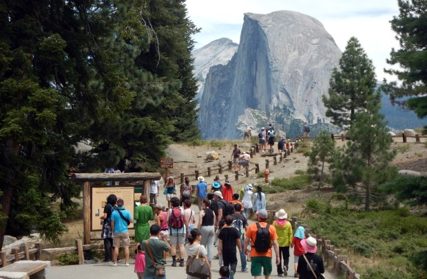 This Aug. 5, 2015 photo shows tourists walking out to Glacier Point with a background view of Half Dome at Yosemite National Park.