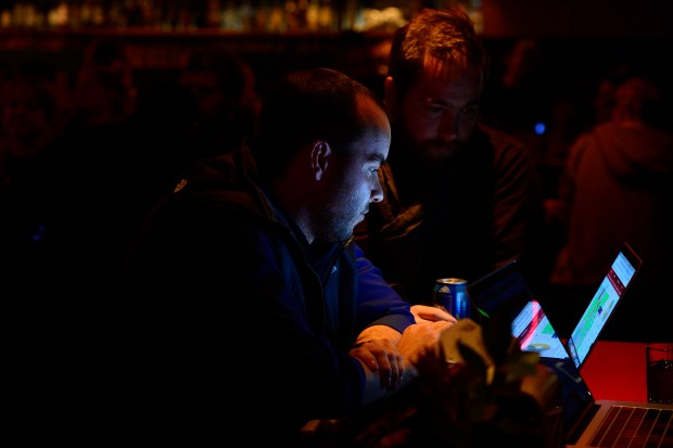Jason Harrison, left, and Tyler Van Kirk, both with Colorado Rising carefully monitor results during a watch party for supporters for Proposition 112 at Big Trouble Restaurant inside Zeppelin Station on November 6, 2018 in Denver, Colorado.