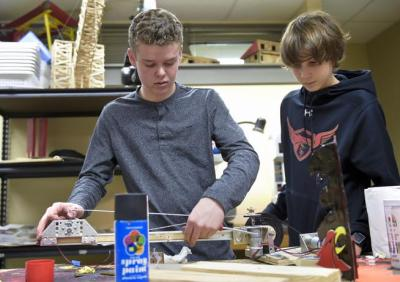 Skyline High robotics team members Connor Kelso, left, and Ryan Messinger work on a robot at the school on Thursday. (