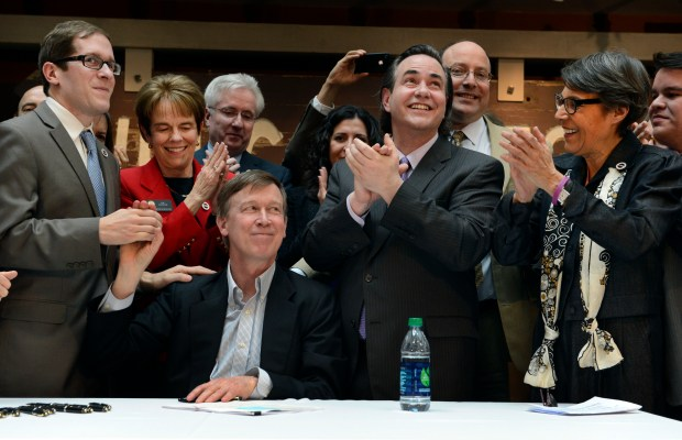Governor John Hickenlooper, seated, celebrates with ...