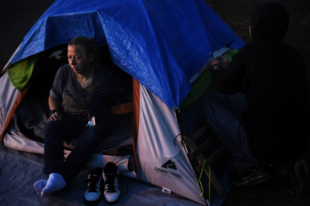 DENVER, CO - MARCH 20: Alice Fria, 57, and tentmate Ron Doss, 43, settle in Denver, Colorado on March 20, 2019.  If you put it all in, you will be safe, warmer at night, and your area cleaner, while you survive on the streets of Denver.  (Photo by Joe Amon / The Denver Post)