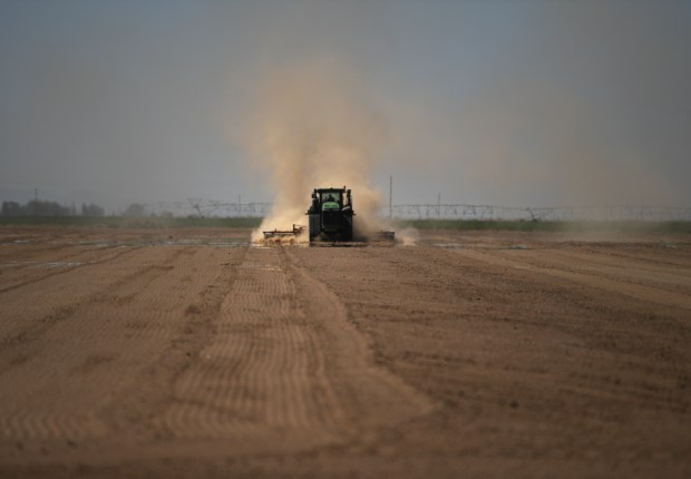 A farmer plows his field near ...