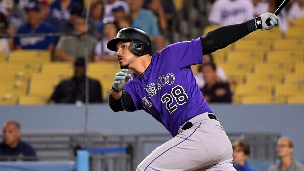 Colorado Rockies' Nolan Arenado, left, hits ...