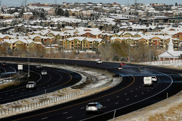 Cars drive along E-470 toll road ...