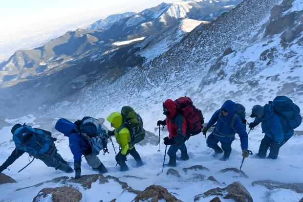 Climbers carefully walk along a ridge ...