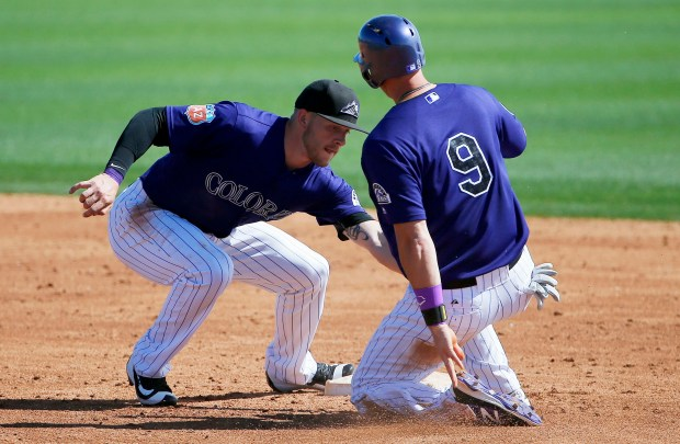 Colorado Rockies' Trevor Story, left, tags ...