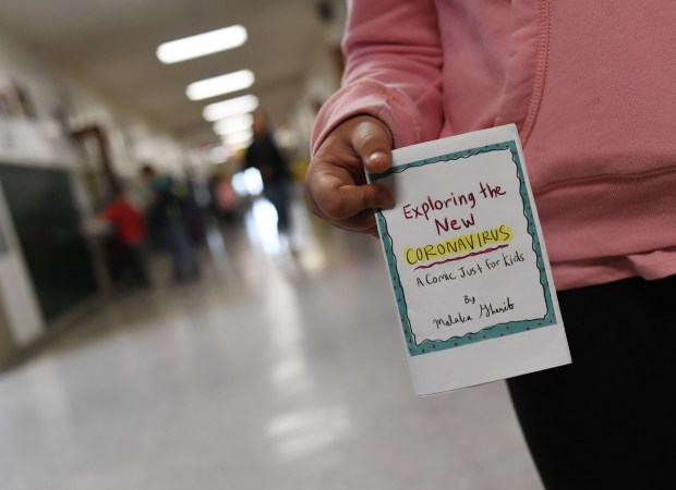 A second-grader holds a copy of ...