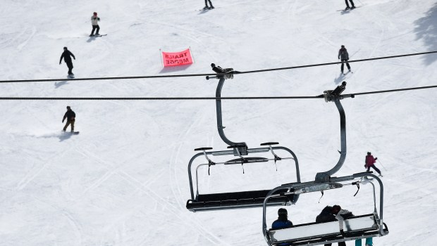 Skiers and snowboarders head down a ...