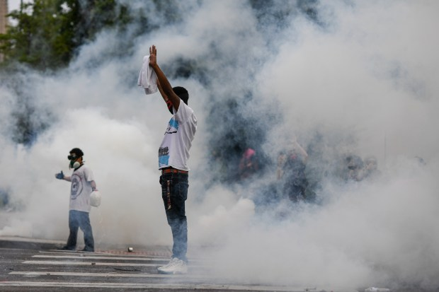A protestor stands in a cloud ...