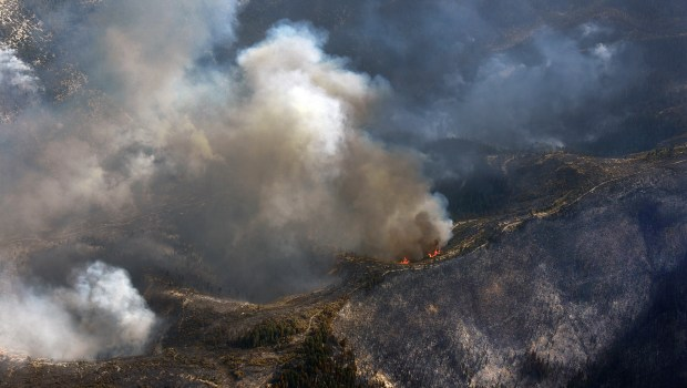 Flames and smoke rise along a ...