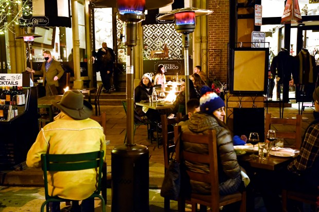 Patrons dine outdoors near heaters and ...