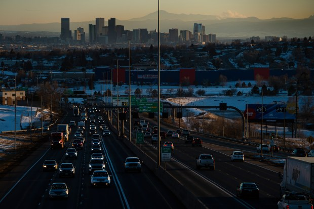 The Denver skyline is seen while northbound traffic drives on Interstate 25 on Tuesday, Dec. 15, 2020, in Thornton, Colo.