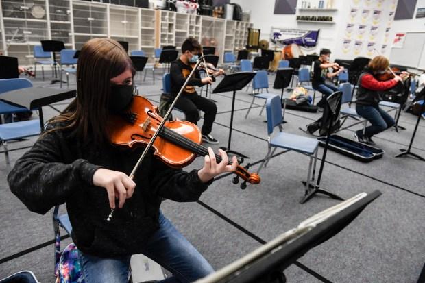 Orchestra student Madisyn Deidel plays her ...