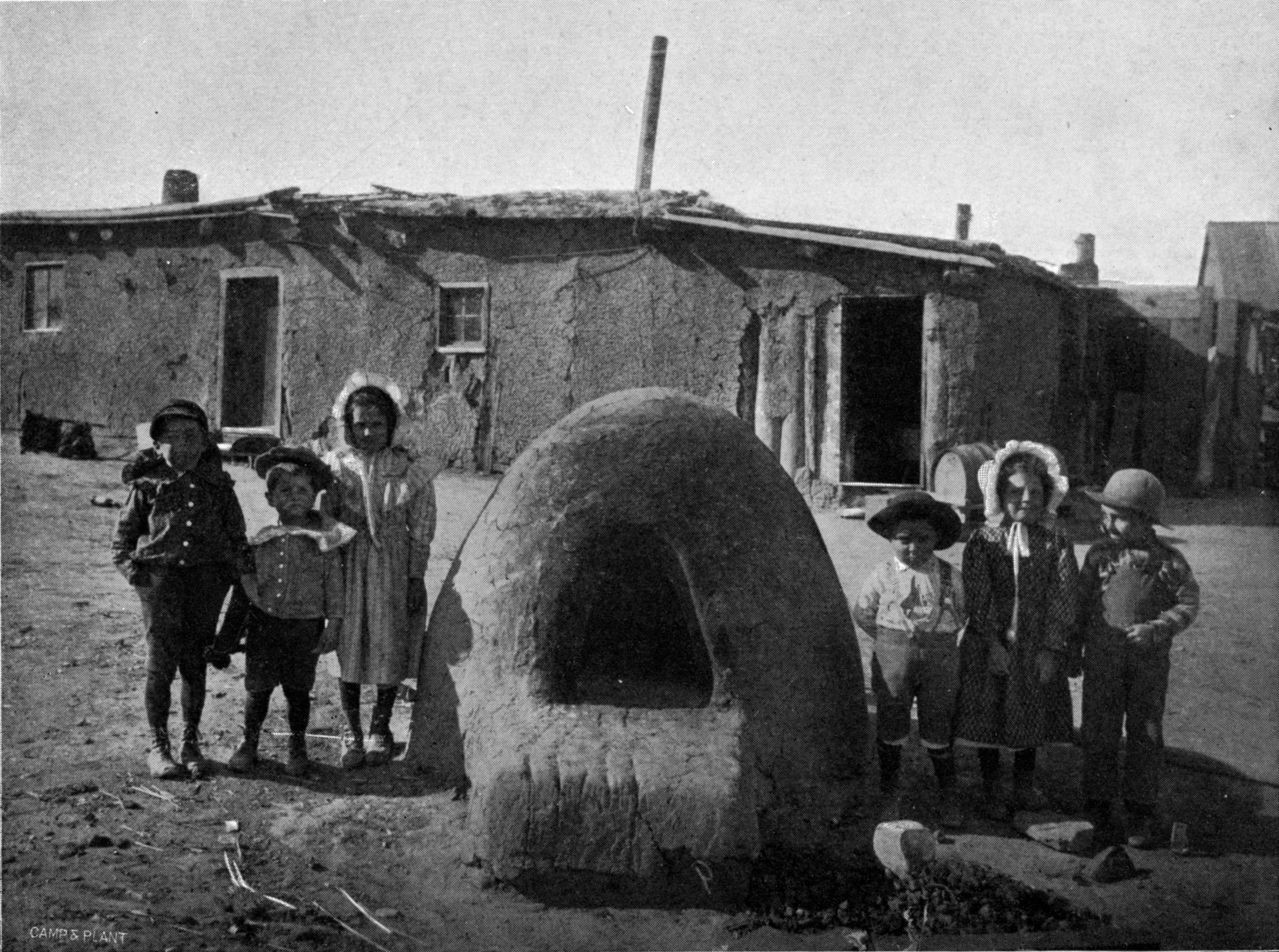 Children with an adobe horno in southern Colorado.