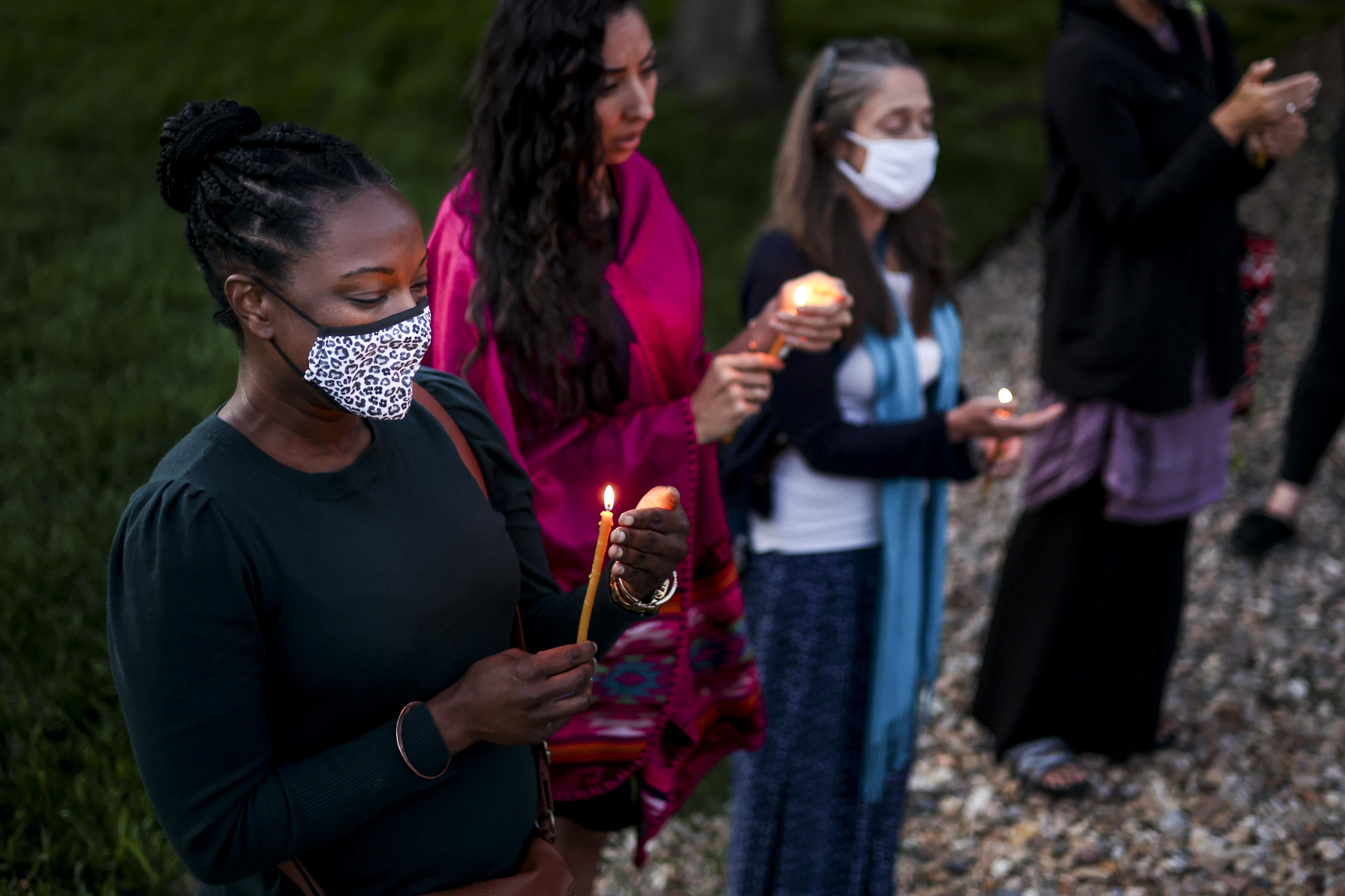 Denise Davis, left, holds a candle ...