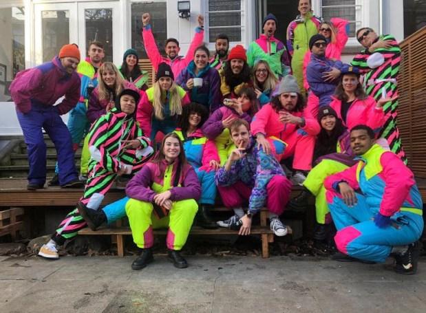 A group of people wearing neon, onesie dress-ups